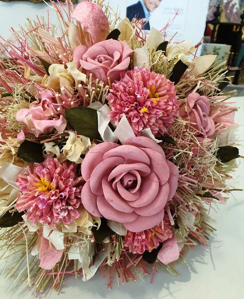 En buket i lyserøde nuancer bundet af tørrede blomster.