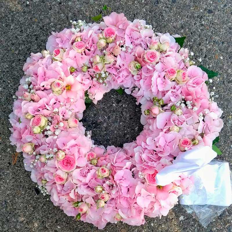 Begravelseskrans i lyserøde nuancer.