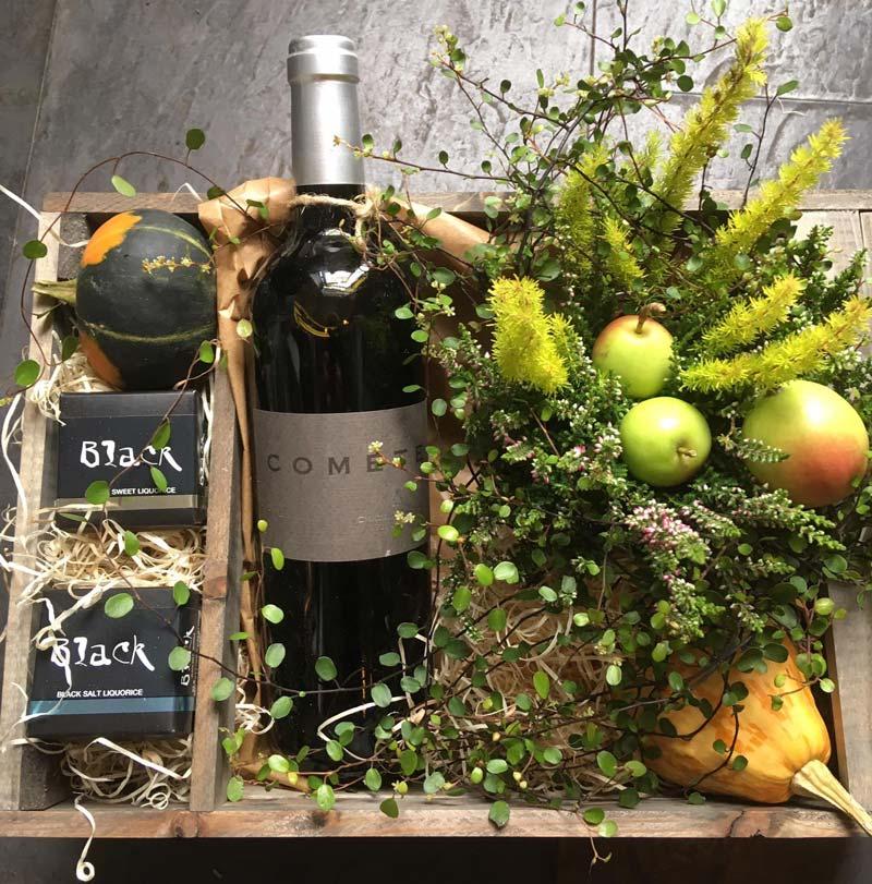 Gavekasse med vin, lakrids og planter.