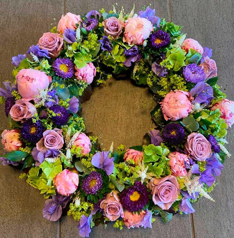 En rundpyntet begravelseskrans i lyserød, blålilla og lime farver.