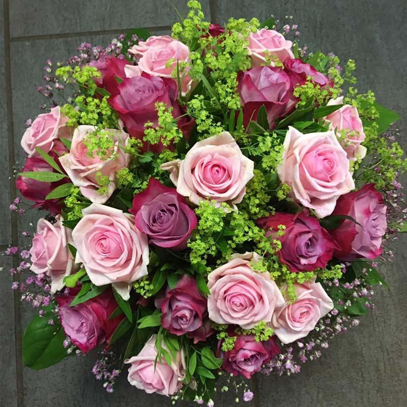 En smuk rund brudebuket med lyserøde og lilla roser og brudeslør.
