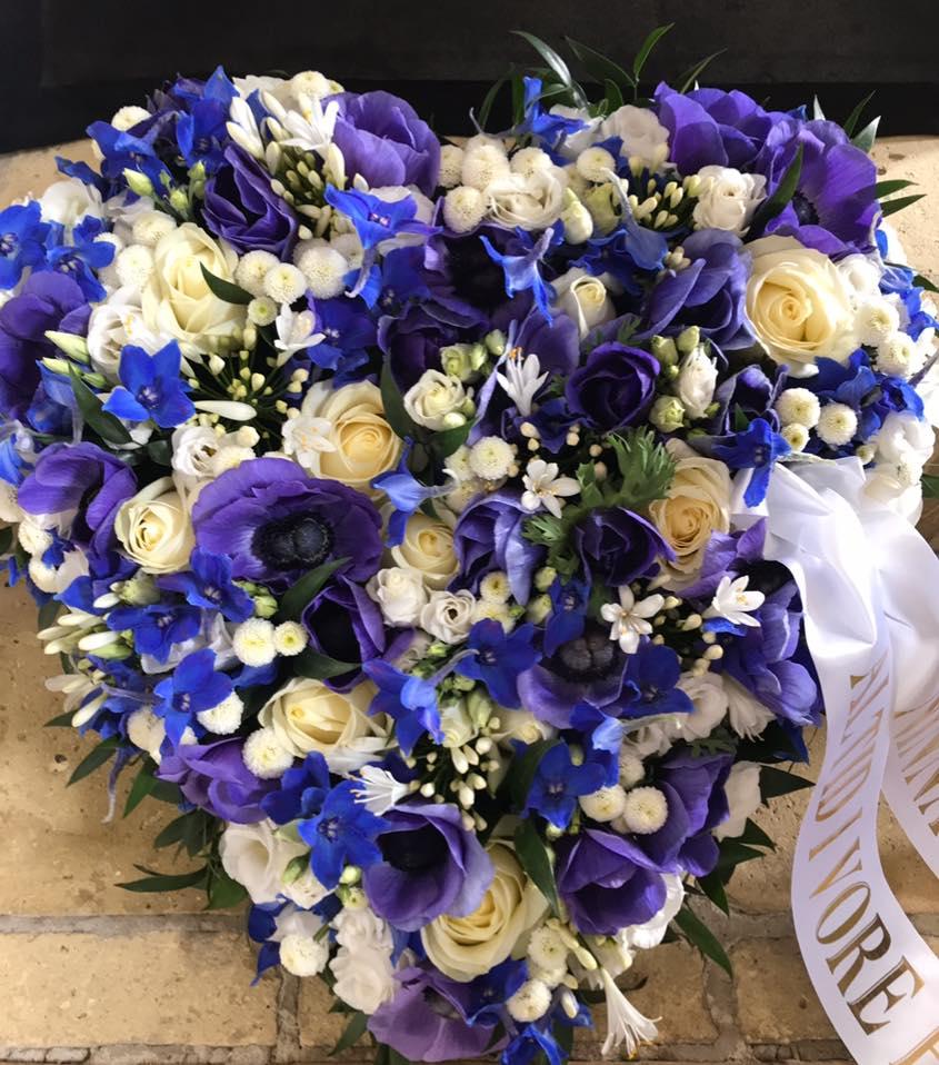 Begravelseshjerte af blå og hvide blomster