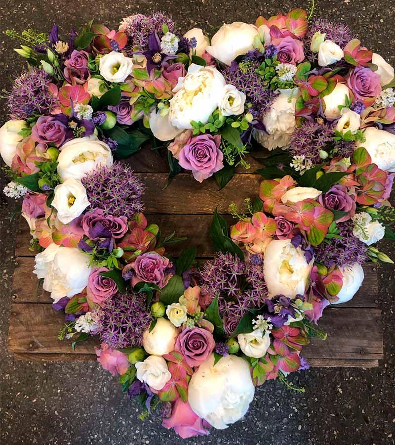 Begravelseshjerte i hvid, lilla og grøn, fra Masielas Blomster