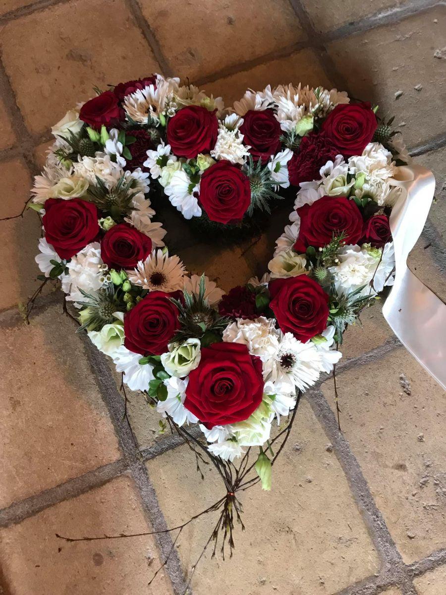 Åbent begravelseshjerte med røde og hvide blomster